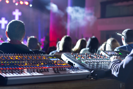 Soundman working on the mixing console in concert hall. Hands on the sliders. Stock Photo