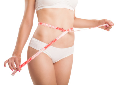 Slim body of woman with a measuring tape.