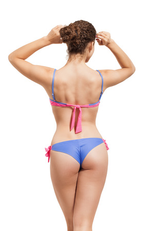 female sexuality: Slender girl in a swimsuit isolated on white.
