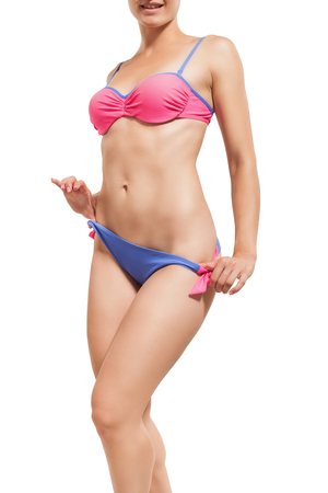 Slender girl in a swimsuit isolated on white.