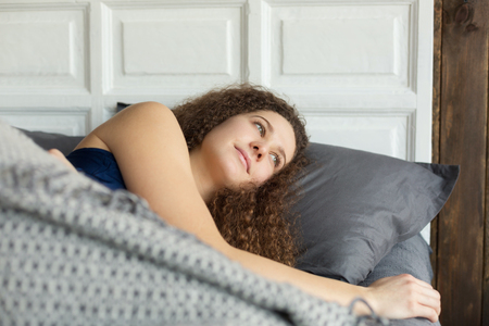 Young girl lying in bed Stock Photo