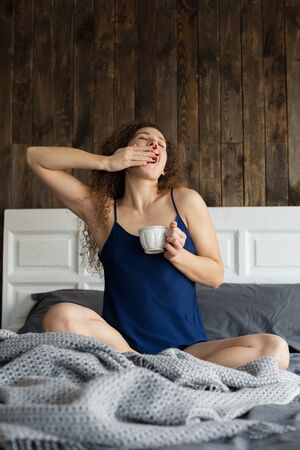young caucasian girl drinking coffee sitting on the bed