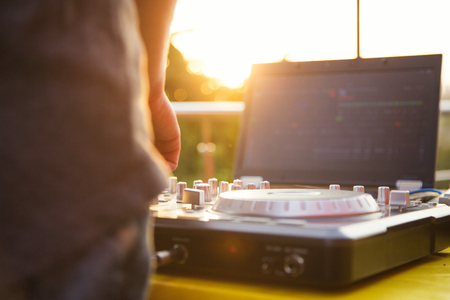 Dj mixing music outdoor. DJ stands near the control panel. Stock Photo