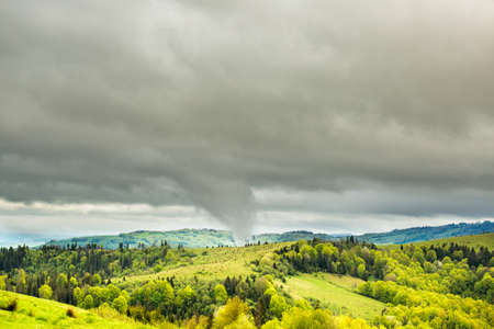 Tornado tip touching mountain. Small portion of green meadow and trees are seen in the foreground. Bad weather that can cause damage. Stock Photo