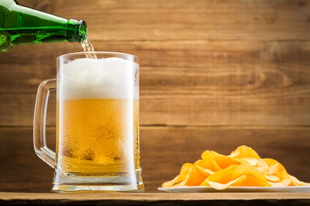 Filling a glass with beer on the background of a wooden wall. Potato chips lie on the white plate near to the glass.