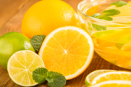 Glass bowl with detox water with slices of orange and lime.  Close-up. Bowl and fruit on a wooden table. Stock Photo