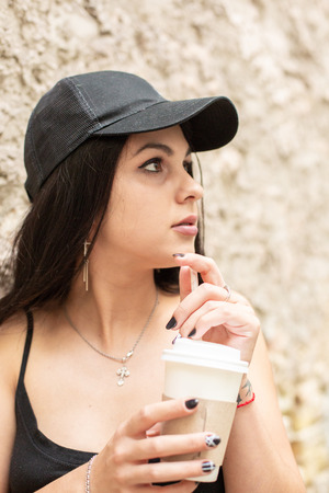 Beautiful young girl drinks coffee from a paper cup through a straw near a brick wall.