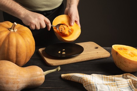 The cook separates the grain from the pumpkin cut in half.