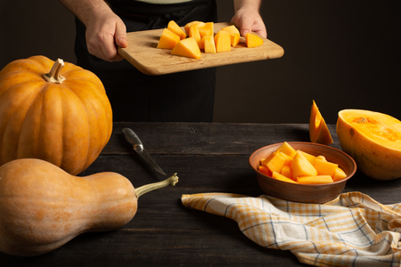 Cook throws slices of pumpkin from a cutting board into a deep bowl.