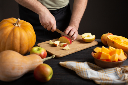 The cook cuts the apple into pieces for baking. On a wooden black table lie pumpkins of various sizes and shapes, ripe apples, a dishcloth and a bowl of sliced pumpkin.