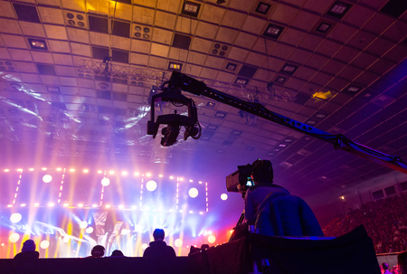 Television broadcast by a cameraman during a concert. Camera with the operator is on the high platform. Silhouettes on the background of colorful beams. Stock Photo