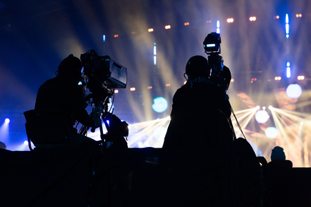 A group of cameramen working during the concert. Television broadcast event. Silhouettes of workers against the background of colorful beams. Banque d'images
