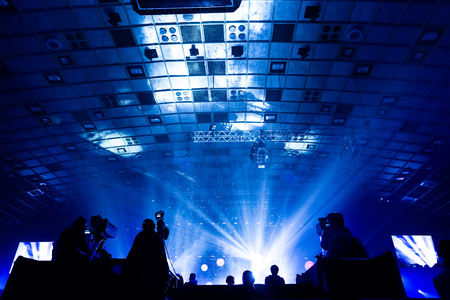 A group of cameramen working during the concert. Television broadcast event. Silhouettes of workers against the background of colorful beams. Foto de archivo