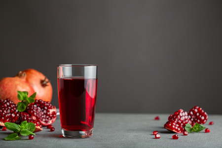 Pomegranate juice in a glass on gray background.