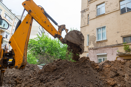 Excavator bucket pours ground. Repair work plumbing in the courtyard of a residential building.