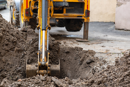 Excavator digs a trench. Repair work in the courtyard of a residential building. Stockfoto