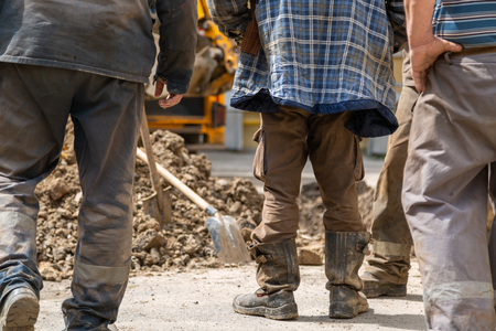 A group of workers stand near an open pit in dirty clothing. Repair of plumbing.