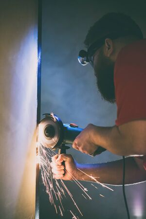 A man repairs a door in the basement of his house using a manual grinding machine.