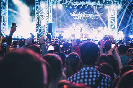 Viewers watch a rock band perform on stage.