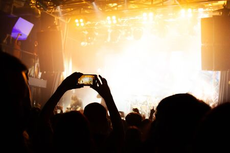 Silhouettes of a concert crowd with smartphones in their hands.