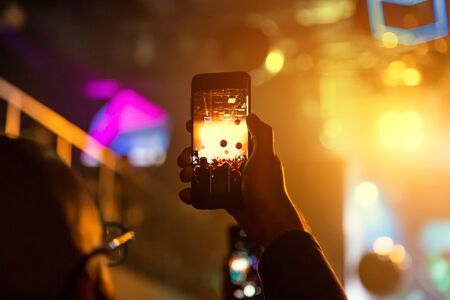 The viewer in a nightclub takes a concert on a smartphone.