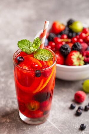 Fresh summer berry drink with lemon and mint. One glass with a beverage and a bowl of fruit on a gray stone table. Place for text. Top view.