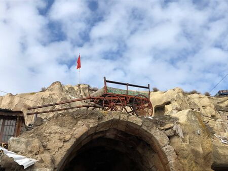 An old cart on the edge of a stone wall. A poor Turkish village in the Cappadocia region.