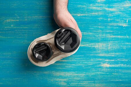 Two disposable paper cups of coffee and a cup holder in a male hand on a blue wooden background. Cups of different sizes. Top view. Concept: Food Delivery. Takeaway. Coffee to go.