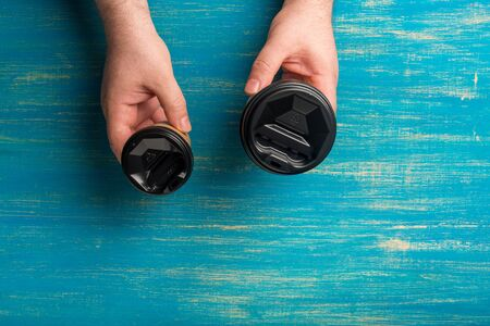 Two disposable paper cups for coffee in a male hand's on a blue wooden background. Cups of different sizes. Top view. Concept: Food Delivery. Takeaway. Coffee to go. Imagens