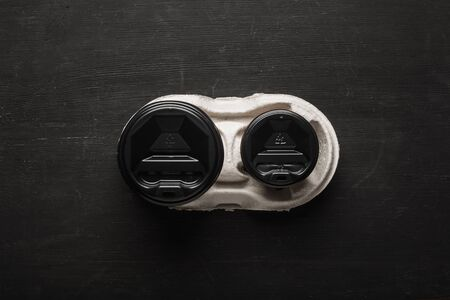 Two disposable paper cups of coffee and a disposable cup holder on a black wooden background. Top view. Concept: Food Delivery. Takeaway. Coffee to go. Imagens