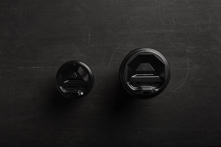 Two disposable paper cups different size of coffee on a black wooden background. Top view. Concept: Food Delivery. Takeaway. Coffee to go.