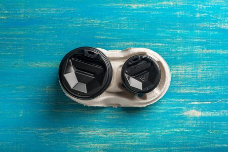 Two disposable paper cups of coffee and a disposable cup holder on a blue wooden background. Top view. Concept: Food Delivery. Takeaway. Coffee to go. Imagens