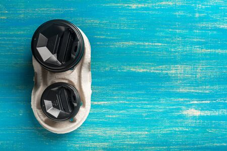 Two disposable paper cups of coffee and a disposable cup holder on a blue wooden background. Top view. Concept: Food Delivery. Takeaway. Coffee to go. Imagens - 147366046
