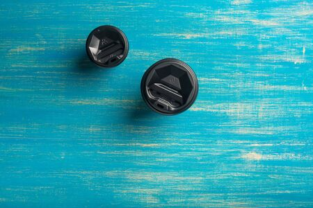 Two disposable paper cups different size of coffee on a blue wooden background. Top view. Concept: Food Delivery. Takeaway. Coffee to go. Imagens