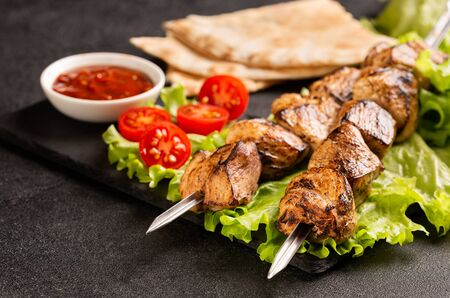 Two portions of shish kebab on a stone plate with salad.