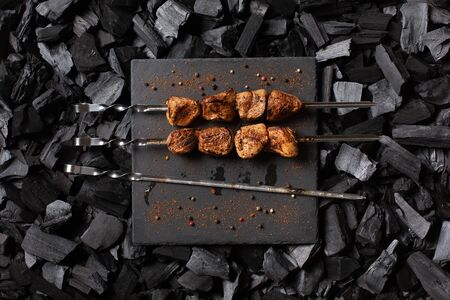 Kebab on skewers. Two portions of grilled meat on a stone plate and one empty skewer.