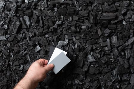 Charcoal background. Hand holds a gray card to set white balance. Black texture. Copy space. Top view. Imagens - 147934435