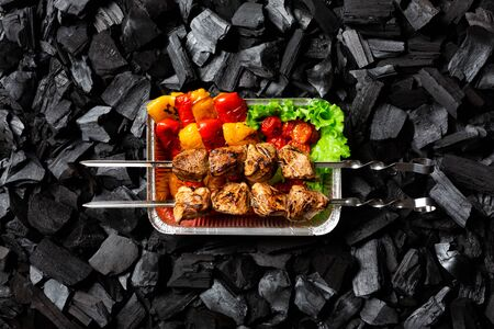 Ready shish kebab. Grilled vegetables and meat on skewers in an aluminum disposable container.