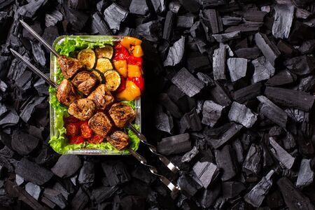 Ready shish kebab. Portion of grilled meat and vegetables in a disposable container on charcoal background. Copy space. Imagens - 149526700