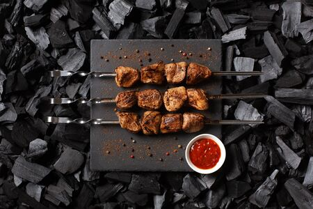 Shish kebab on skewers. Three portions of grilled meat on a stone plate, spicy and sauce. Charcoal background. Top view.