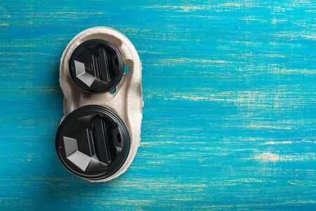Two disposable paper cups of coffee and a disposable cup holder on a blue wooden background. Imagens - 149657389