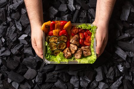 Ready shish kebab. Portion of grilled meat and vegetables in a disposable container in male hands.
