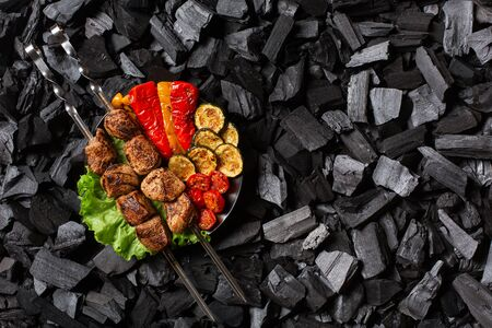 Shish kebab on skewers and grilled sweet pepper, zucchini, cherry, tomato on a round plate. Charcoal background.