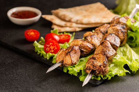 Two portions of shish kebab on a stone plate with salad. Imagens - 148106497