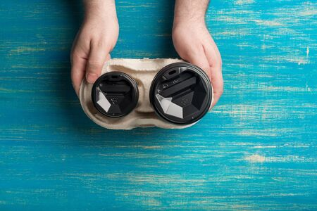 Two disposable paper cups of coffee and a cup holder in a male hands on a blue wooden background.