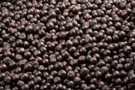 Frozen fresh chokeberry. Food background. Top view.