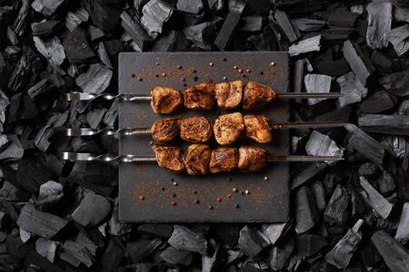 kebab on skewers. Three portions of grilled meat on a stone plate. Charcoal background. Top view. Imagens - 148108298