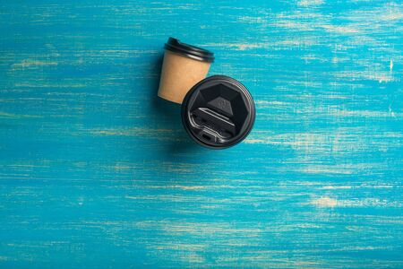 Two disposable paper cups different size of coffee on a blue wooden background. Top view. Concept: Food Delivery. Takeaway. Coffee to go. Imagens - 148114134