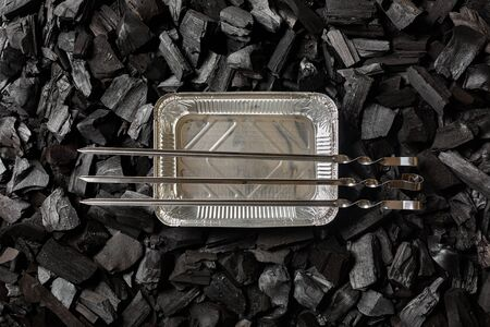 Empty aluminum foil disposable container on charcoal. Three empty skewers. Top view.