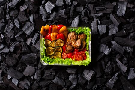 Ready shish kebab. Portion of grilled vegetables - sweet pepper, zucchini, cherry, tomato and meat in a aluminum foil disposable container on charcoal background. Top view. Imagens